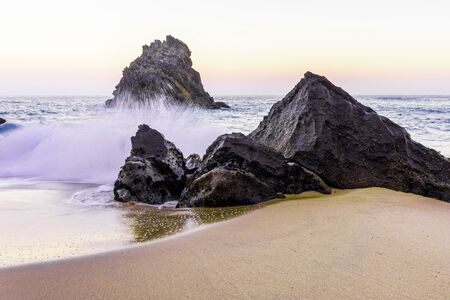 Rocky and sandy beach at sunrise, Portugal.