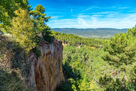 Roussillon, Provence, France: landscape at dawn of the reds ochre rocks and the green valley in the nature park of Luberon