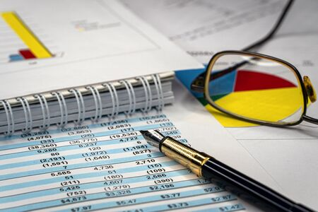 Accounting business concept. Glasses and pen with accounting report and financial statement on desk.
