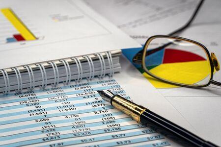 Buchhaltungsgeschäftskonzept. Brille und Stift mit Buchführungsbericht und Jahresabschluss auf dem Schreibtisch.