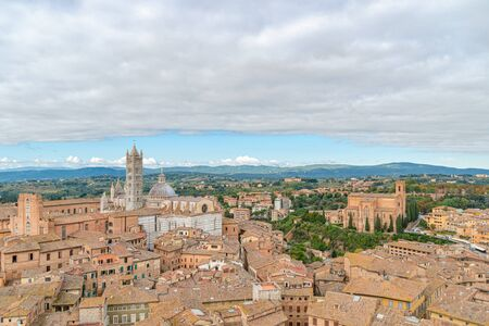 Beautiful aerial panoramic view of Old Town of medieval city of Siena in the cloudy autumn day, Tuscany, Italy Archivio Fotografico