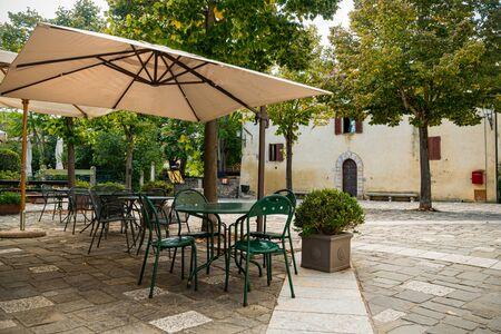 Sillas y mesas de restaurante vacías en la antigua calle italiana. Región de Toscana. Foto de archivo