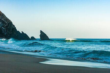 Breaking ocean wave falling down at sunrise time landscape. Sunrising sunlight on surf waves Stock Photo