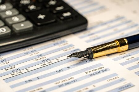 The report summarizes the results of business operations, pen, calculator on desk of investor. Financial business planning