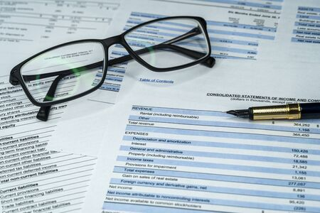 Income statement financial report with pen and glasses. Investment analysis