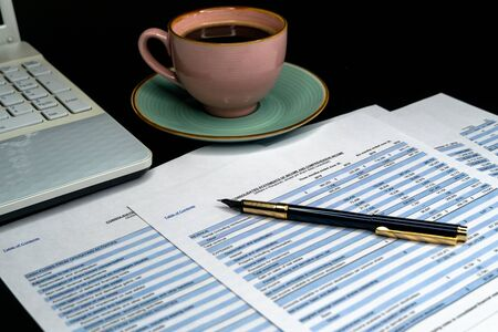 The report summarizes the results of business operations, pen, cup of coffee on desk of investor. Financial business planning