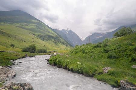 Mountain river stream landscape with dramatic cloudy sky