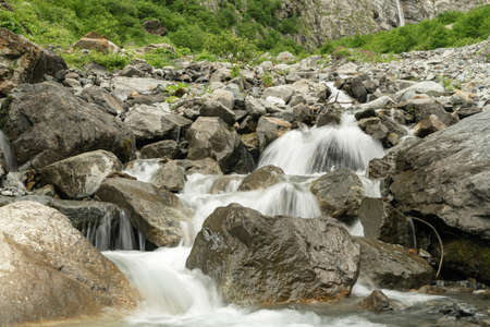 Water flows over rocks at the bottom of a mountain waterfall. Beautiful mountain river Reklamní fotografie