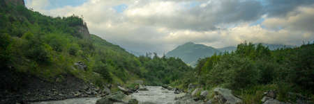 Mountain river stream landscape with dramatic cloudy sky at sunset. Wide banner background Reklamní fotografie