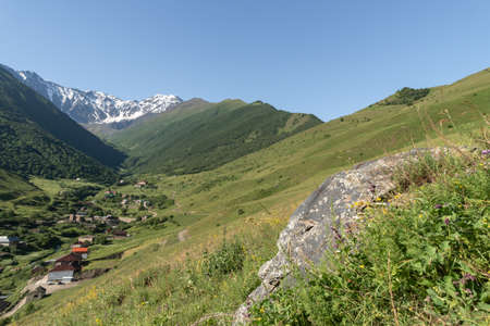 Mountain landscape with green meadow and mountain village in valley. Mountain valley panorama Reklamní fotografie