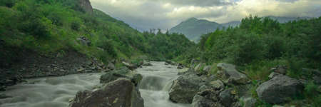 Mountain river stream with long exposure shot. Landscape with dramatic cloudy sky at sunset in Caucasus. Wide banner background