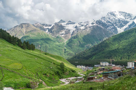 View of highest mountain village in mountains with cloudy sky. Beautiful landscape Caucasus.