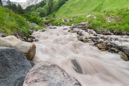 Water in mountain river from glacier on valley. Beautiful landscape Caucasus. Long exposure shot