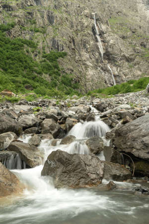 Water flows over rocks at the bottom of a mountain waterfall. Beautiful mountain river Reklamní fotografie - 151903413