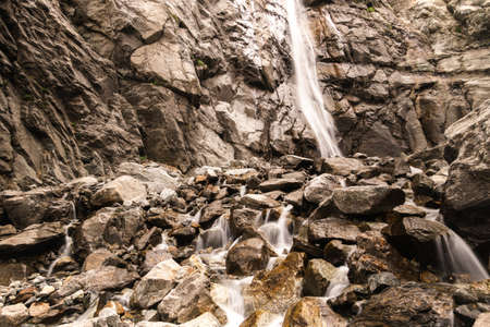 Water flows over rocks at the bottom of a mountain waterfall. Reklamní fotografie