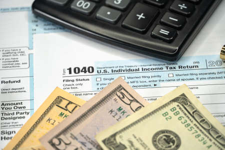 Blank Form 1040 US Individual Income Tax Return with Pen and banknotes. Tax Payment Concept. Selective focus