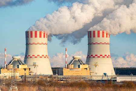 Nuclear power plant cooling towers emissions of steam in the air atmosphere. Industrial zone