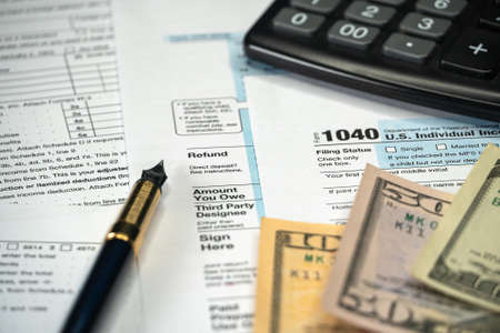 Blank Form 1040 US Individual Income Tax Return with Pen and banknotes. Tax Payment Concept. Filing Taxes Document