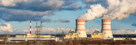 Nuclear power plant with Cooling towers of Atomic energy power station with emission of steam in the air atmosphere. Wide banner