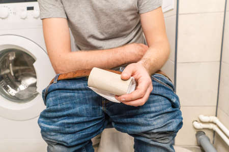 Man sit on bowl toilet with empty roll of toilet paper. Diarrhea attack. Problems with digestion. Food poisoning