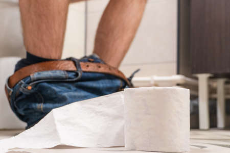 Man sitting on toilet sit bowl with toilet paper, man suffering from diarrhea on toilet bowl at home.
