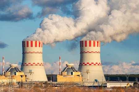 Cooling tower with steam clouds on Atomic nuclear power station Reklamní fotografie
