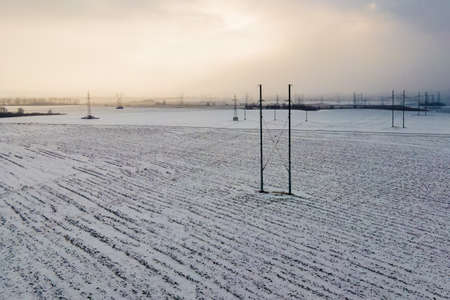 Industrial high voltage electricity tower in snow field at winter.