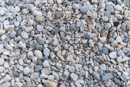 Pebbles beach on sea surface with gray stones: Abstract Composition for background and texture.