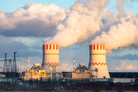 Nuclear power plant and Cooling tower of Atomic nuclear power station. Industrial zone with nuclear plant with emission of steam in the air atmosphere.