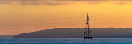 Industrial high voltage electricity tower with sky sunrise. Wide banner Stock fotó