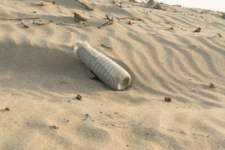 Plastic bottle left on sand of beach. Garbage polluting the natural environment and pollution
