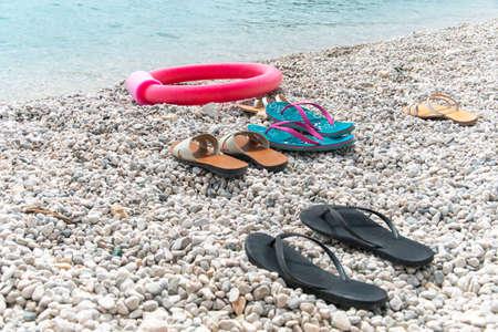 Beach scene. Pairs of flip flop sandals lying on on sea pebble beach