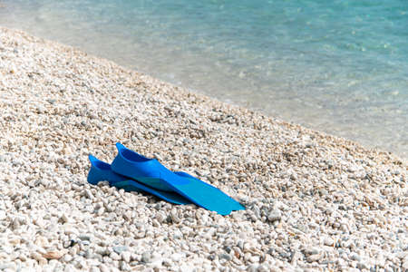 Flippers blue color on pebble beach. Snorkeling equpment in sea.