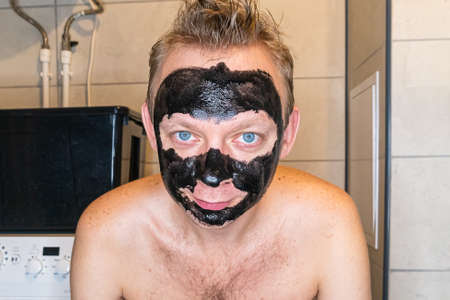 Portrait of man with black cosmetic mask shows on his face in the bathroom, skin problems, care man concept Stock fotó