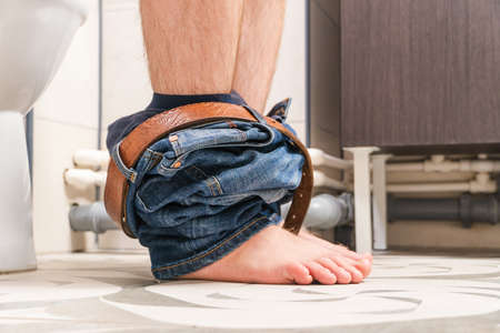 Man sitting on toilet sit bowl, man suffering from diarrhea on toilet bowl at home.