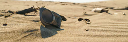 Old rusty beverage can in the sand desert. Pollution of nature recycle the trash. Environment Global problem