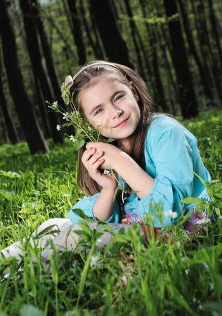 florecitas: Niña sentada en una hierba en el bosque  Foto de archivo
