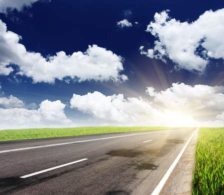 roadway: Empty road with cloudy sky and sunlight