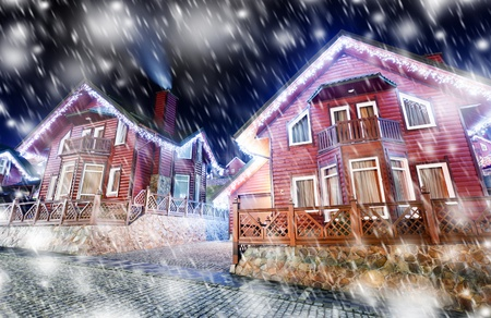 snowfalls: Houses decorated and lighted for christmas at night Stock Photo