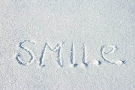 sunny cold days: Word smile written on fresh snow
