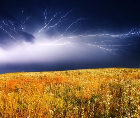 Tormenta con rayos en el prado verde Foto de archivo