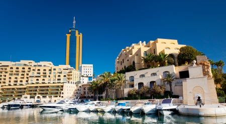 Fantastic city landscape on the seaside with boats. Portomaso Business Tower, Malta. photo