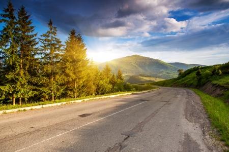 Leere Asphaltstraße mit bewölkten Himmel und Sonnenlicht