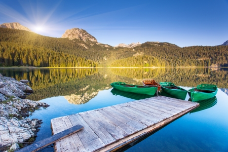 montenegro: Reflection in water of mountain lakes and boats. Black lake in Durmitor national park in Montenegro, Europe. Beauty world. Stock Photo