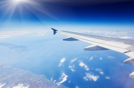 Wing of airplane flying above the clouds in the sky Stock Photo - 21227752
