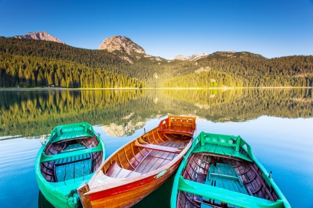 Reflection in water of mountain lakes and boats. Black lake in Durmitor national park in Montenegro, Europe. Beauty world. photo
