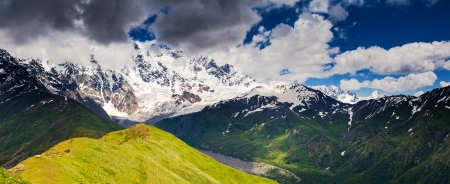 shkhara: Alpine meadows with dramatic sky at the foot of  Mt. Shkhara. Upper Svaneti, Georgia, Europe. Caucasus mountains. Beauty world. Stock Photo