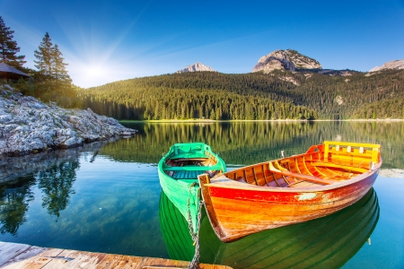 rivers mountains: Reflection in water of mountain lakes and boats. Black lake in Durmitor national park in Montenegro, Europe. Beauty world. Stock Photo