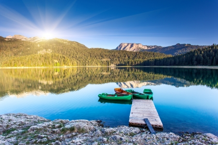 nature landscape: Reflection in water of mountain lakes and boats. Black lake in Durmitor national park in Montenegro, Europe. Beauty world. Stock Photo