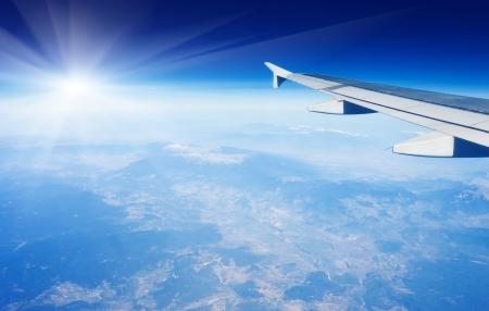 Vleugel van vliegtuig vliegt boven de wolken in de lucht Stockfoto